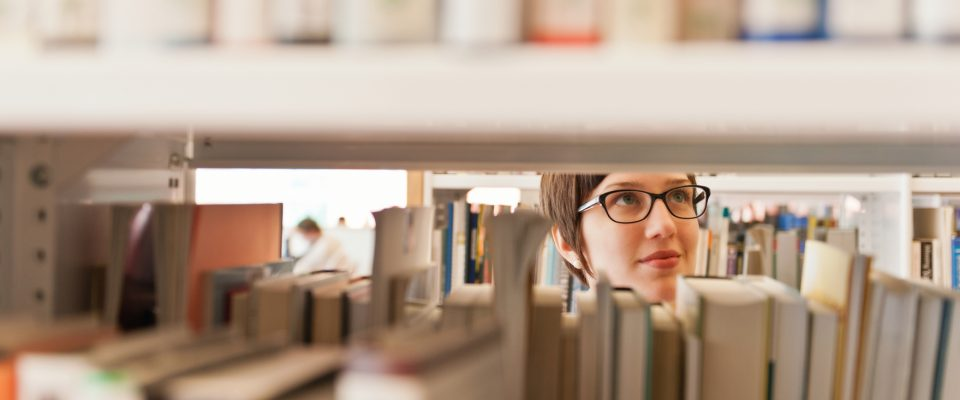 a glimpse of a woman through the library stacks
